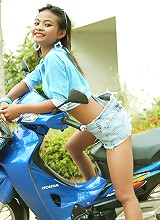 Cute little Thai nubile Tussinee poses on a motorbike